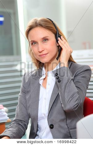 Blond office worker with headphones