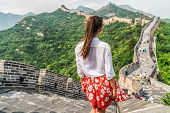 Young girl tourist from behind looking at view of Great Wall of China at famous Badaling tourism att poster