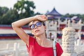 Female asian tourist exhausted during famous attraction visit vacation. Woman wearing sunglassses sw poster