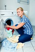 picture of washing-machine  - A young housewife with washing machine and clothes - JPG