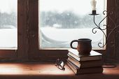 Warm and comfy winter concept. Book, cup of tea and candlestick on wooden window sill in old house.  poster