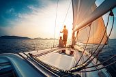 Couple enjoying sunset from the deck of the sailing boat moving in a sea poster