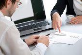 picture of business-partner  - Image of two business partners discussing documents lying on the table - JPG
