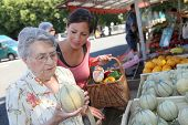 stock photo of grocery-shopping  - Young woman helping elderly woman with grocery shopping - JPG