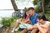Постер, плакат: Семья на велосипеде глядя на карту