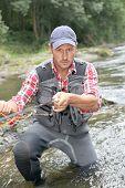 Постер, плакат: Рыбак в реке с fly рыболовная удочка