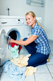 foto of washing-machine  - A young housewife with washing machine and clothes - JPG