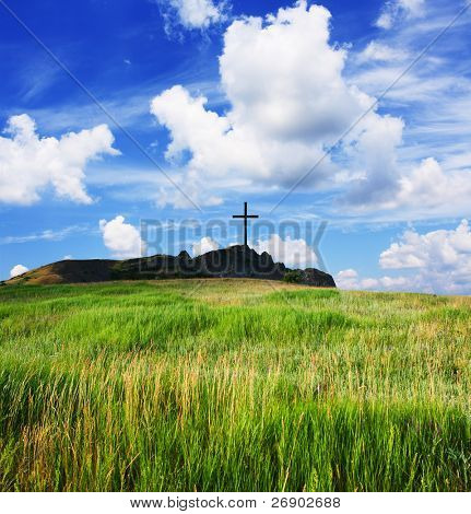Religious cross on a beautiful green hill