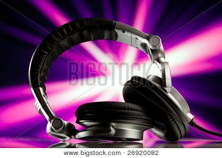 headphones against purple rays background
