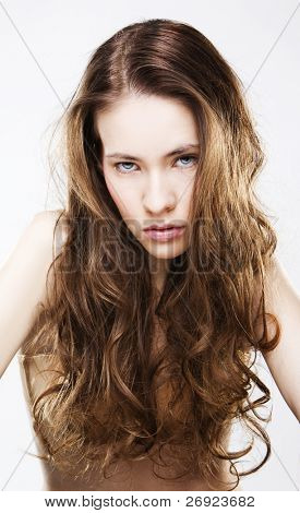 Portrait of long haired young woman with highlighted brown hair, isolated on white background.