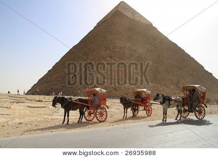 PYRAMIDS OF GIZA, EGYPT - MARCH 11: Unidentified Egyptian people offer horse ride under Great pyramids of Giza waiting for tourists March 11, 2010 in Egypt