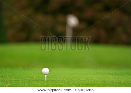 Golf ball on tee with blurry flag in background