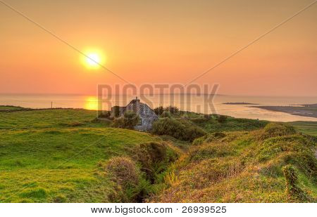 Irish cottage house near ocean at sunset