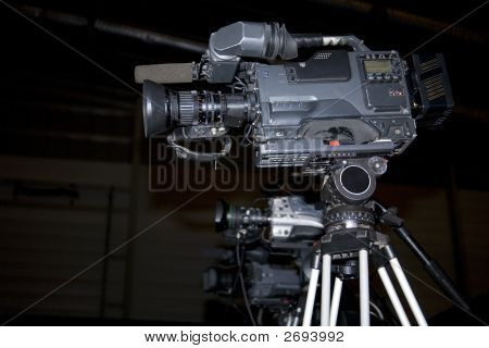 Professional Video Cameras And Tripods On Black Background