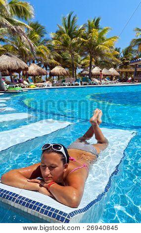 Joven relajarse en las tumbonas de la piscina