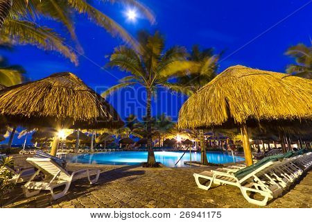 Tropical resort with swimming pool at night