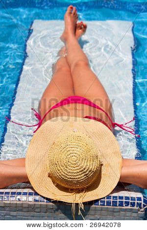 Woman in hat tanning on holiday at swimming pool bed