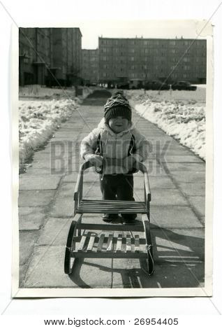 Vintage unretouched photo of young girl with sled