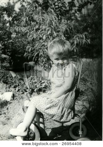 Vintage unretouched photo of young girl on tricycle