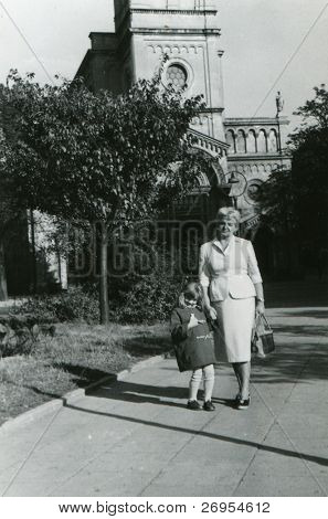 Vintage unretouched photo of mother and daughter walking outdoor