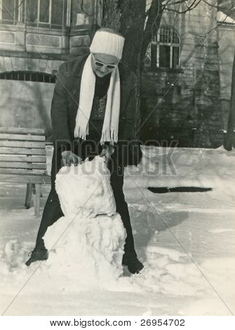 Vintage unretouched photo of woman making a snowman (fifties/sixties)