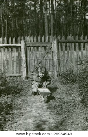 Vintage unretouched photo of young girl with toy wheelbarrow