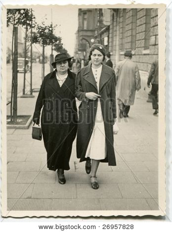 Vintage photo of  mother and daughter walking on the street (thirties)