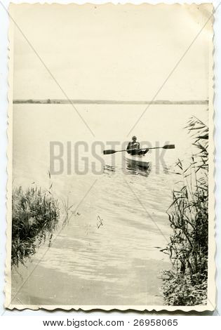 Vintage photo of father and son kayaking together (fifties)