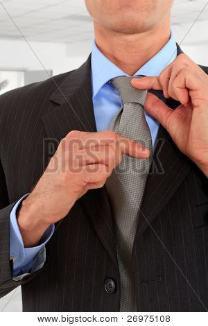 Detail of a businessman correcting a tie