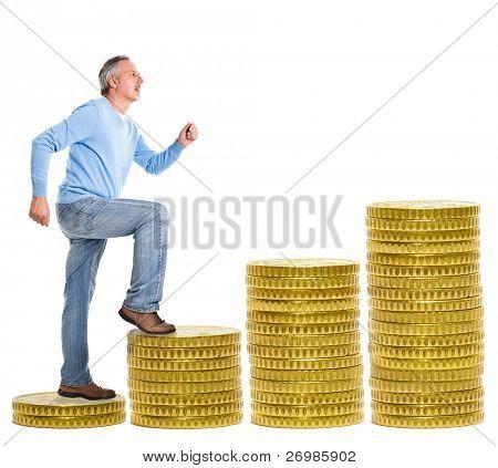 Mature man climbing a stair made of money