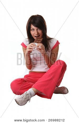 Girl in sports dress eating chocolate