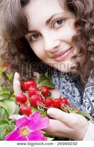 Picture of beautiful girl with a flower in your teeth dog-rose