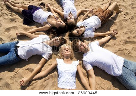 The image of a group of friends, lying on the sand their heads together