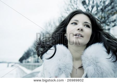 The image of a beautiful girl in the background of a winter city