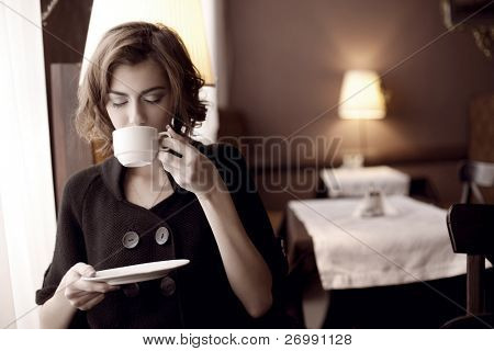 The image of a beautiful girl in a cafe