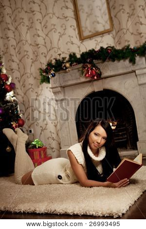 Image of the girl lying near the fireplace and reads a book