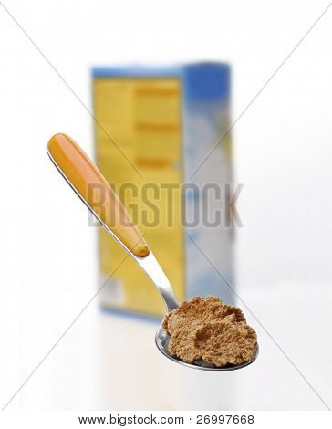 Cereal box and spoon on white background.