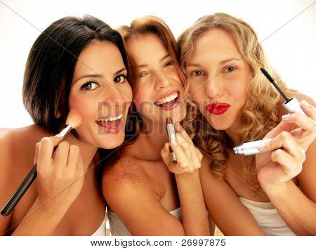 Three young women applying makeup mirror.