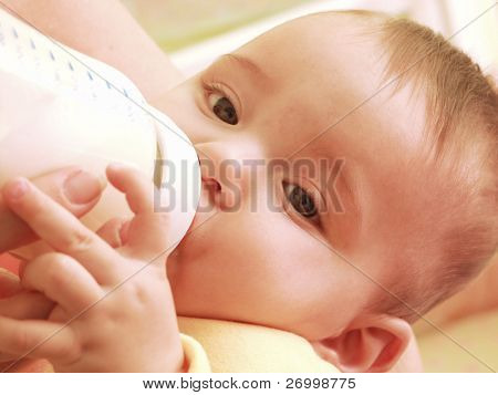 Mother feeding her baby boy with a baby bottle.