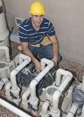 stock photo of blue-collar-worker  - blue collar worker inspecting pool filter pumps - JPG