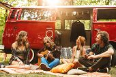 Group of friends hippies men and women playing guitar and sitting near vintage minivan into the natu poster