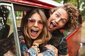 Photo of happy hippie couple smiling, and showing peace sign whi poster