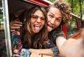 Photo of traveling hippie couple smiling and showing peace sign while driving retro minivan in fores poster