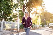 Smiling senior woman jogging on streets in early morning. Active mature woman running on a sunny day poster