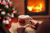 Woman relaxing with a cup of hot chocolate sitting in an armchair by the fireplace and christmas tre poster