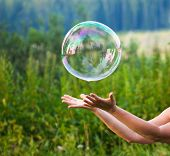stock photo of soapy  - hand catching a soap bubble - JPG