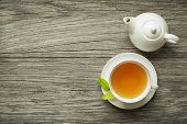 Cup Of Green And Herbs Tea Served With Tea Pot On Wooden Table poster