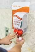 Person Dispensing Disinfectant Sanitizer Liquid Onto Hand At Public Amenities poster