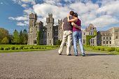 Постер, плакат: Пара в объятия глядя в идиллической Эшфорд замок Ирландия