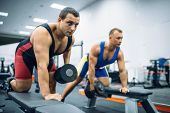 Two weightlifters doing exercise with dumbbells poster